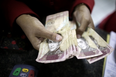 A woman counts bolivar notes as she pays for an electronic item at an store in La Guaira