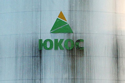 Workers walk under YUKOS oil company logo at Yuganskneftegaz oil processing facility, the core unit ..